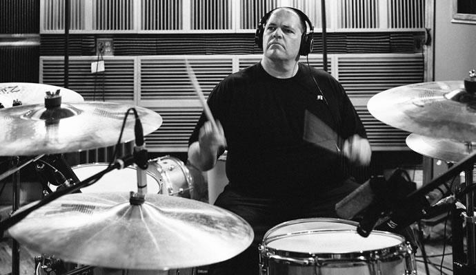 Fotografía blanco y negro de Bill Stevenson tocando batería en estudio