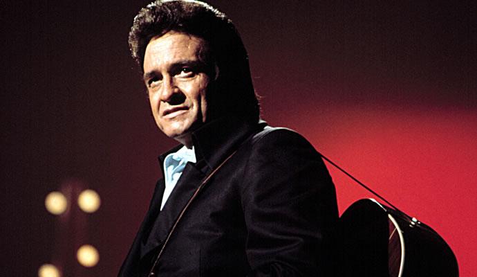 Foto de Johnny Cash con guitarra acústica en su espalda