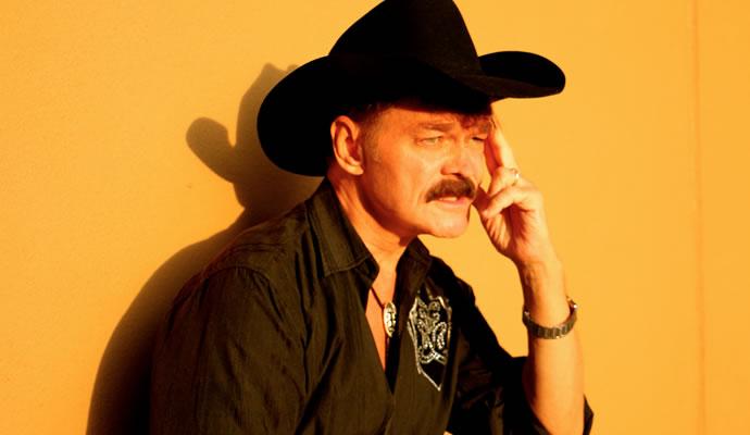 Randy Jones en foto con sombrero negro y fondo amarillo